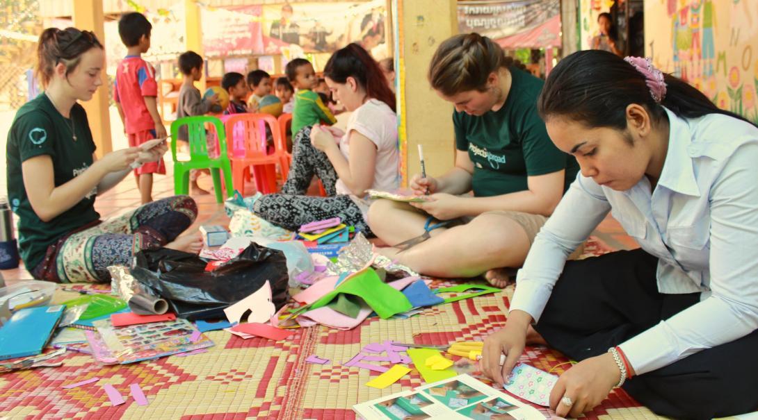 Voluntarias preparando una actividad de manualidades en su programa de voluntariado para jóvenes.
